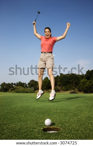 Caucasion mid-adult woman holding golf club jumping in air cheering with golf ball and hole in foreground. - stock photo