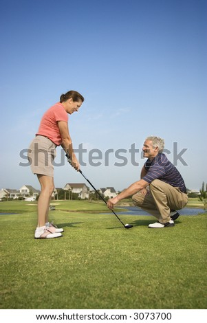 Caucasion mid-adult woman holding golf club while mid-adult man kneels holding club teaching. - stock photo