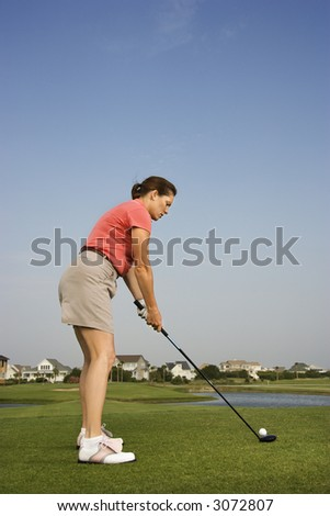 Caucasion mid-adult woman preparing to drive golf ball. - stock photo