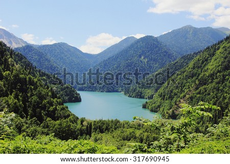 Caucasus. Abkhazia. Riza lake with clear blue water, surrounded by lush green forest against the blue sky with clouds, a sunny summer day - stock photo