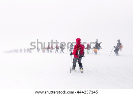 Caucasus, Russia. A huge group of climbers descends from the Elbrus in the fog. The concept of mountaineering in a snow storm - stock photo