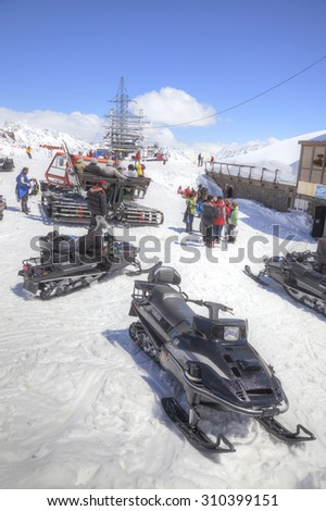 CAUCASUS, RUSSIA - May 01.2015: Snow grooming and snowmobiles next to the station of ropeway on the slope of mountain Elbrus - stock photo