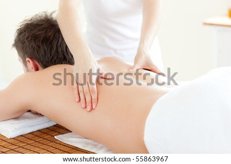 Caucsasian young  man receiving a back massage in a Spa Center - stock photo