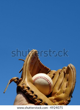Caught baseball in glove portrait photo. Space at top for messaging.