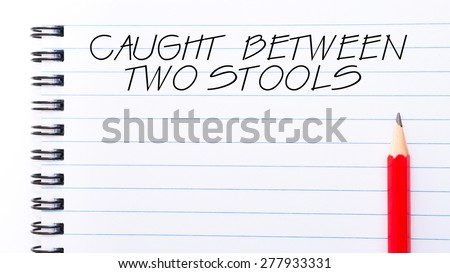 Caught Between Two Stools Text written on notebook page, red pencil on the right. Motivational Concept image - stock photo