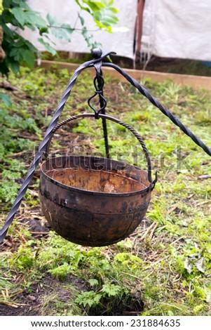 cauldron with a tripod outdoors - stock photo
