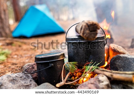 Cauldrons over burning campfire with camping tent in background - stock photo