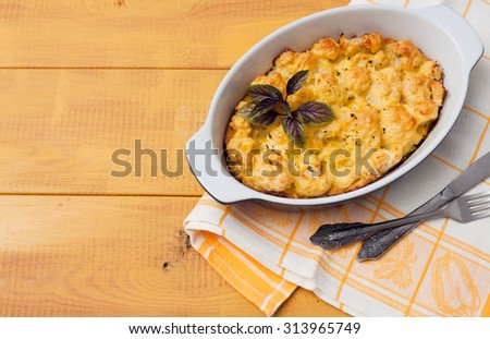cauliflower baked with egg and cheese on wooden background - stock photo