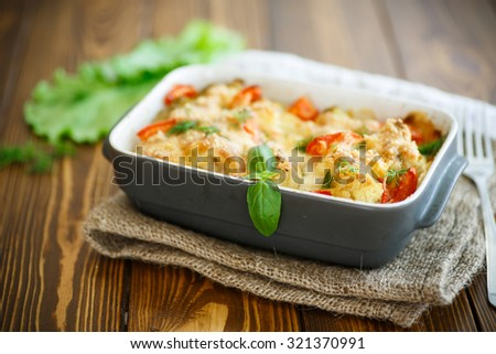 Cauliflower baked with eggs, tomatoes, vegetables and cheese - stock photo