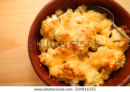 Cauliflower cheese in a baking dish over wooden table background - stock photo