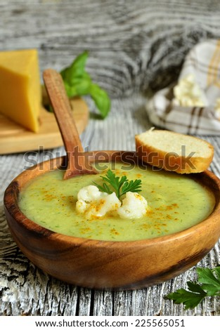 Cauliflower cream soup with cheese,herbs and curry in a wooden bowl.