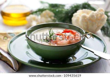 Cauliflower cream soup with skewered prawns - stock photo