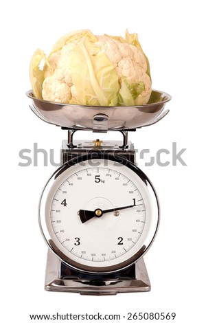 Cauliflower on a scale on white background, concept of natural health food - stock photo