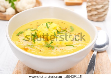 cauliflower soup with curry and cream in a bowl, close-up - stock photo