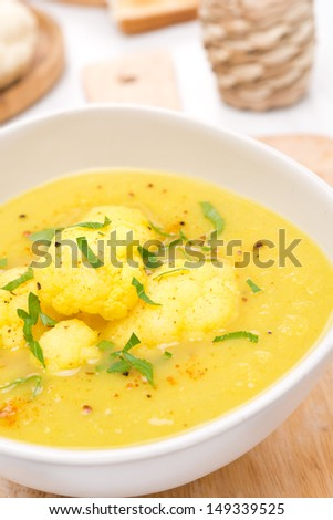 cauliflower soup with curry in a white bowl, close-up, vertical