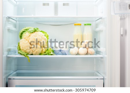 Cauliflower, white eggs, champignon mushrooms and two glass bottles of yogurt on shelf of open empty refrigerator. Weight loss diet concept. - stock photo