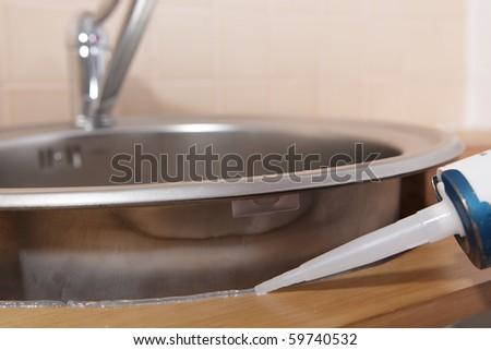 Caulking gun putting silicone sealant to installing a kitchen sink - stock photo