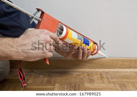 Caulking silicone from cartridge on wooden batten. - stock photo