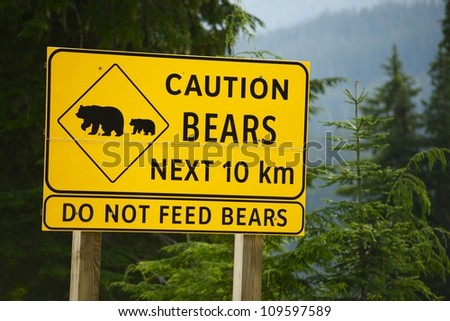 Caution Bears Next 10km - Do Not Feed Bears. Road Side Yellow Sign in British Columbia, Canada. - stock photo
