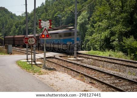 Caution going train!   Motion blurred train passing a railroad crossing, Croatia - stock photo