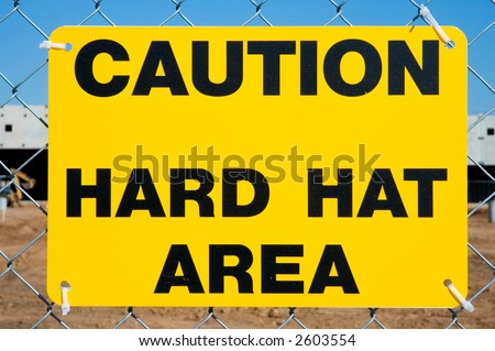 Caution Hard Hat Area Sign On Chainlink Fence - stock photo