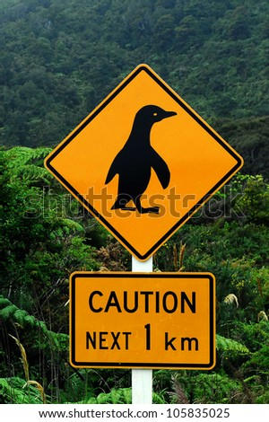 Caution Penguins road sign next 1 km and native bust on southern West Coast of New Zealand. - stock photo
