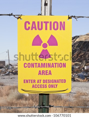 Caution radioactive contamination warning sign with barb wire fence. - stock photo