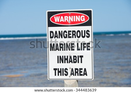 Caution sign and symbol at coastal reef warning of dangerous marine life in ocean, with panoramic seascape, summer sunny blue sky, horizon, copy space. - stock photo