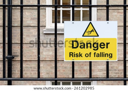 Caution Sign: Danger Risk of Falling on Metal Fence - stock photo