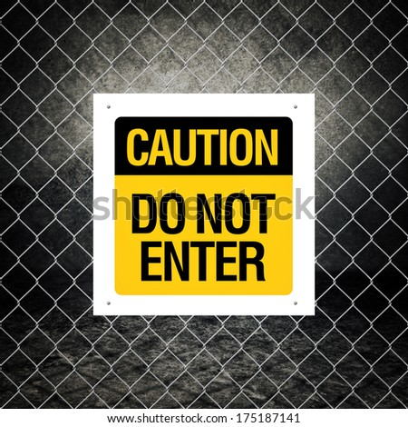 Caution sign - Do not enter on chain link fence - stock photo