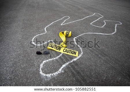 Caution tape and broken sun glasses rest near a chalk line from an auto accident. - stock photo