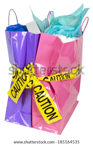 Caution tape over colorful shopping bags on white background, balancing the debt and managing home finances concept image