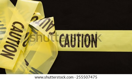 Caution Tape with isolated background on black - stock photo