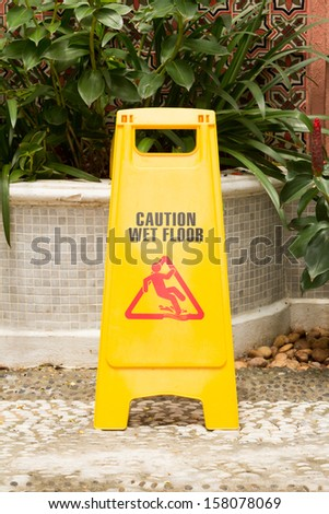 caution wet floor sign in the garden - stock photo