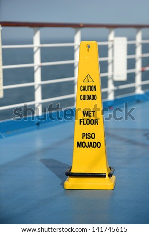 Caution Wet Floor sign on deck of cruise ship