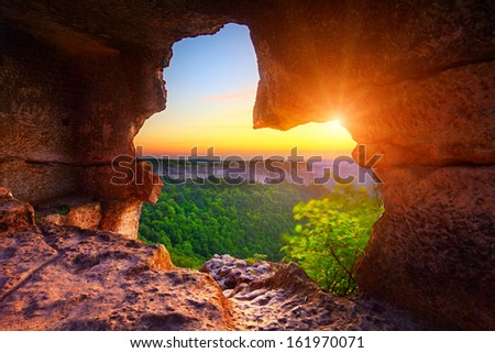 cave and view of canyon at sunset time - stock photo