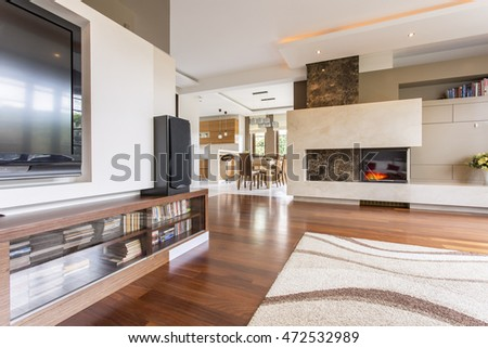 Cavernous living room with a tv set and a marble fireplace joined with a dining room in the background