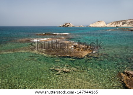 Caves and rock formations by the sea at sarakiniko area on Milos island, Greece - stock photo