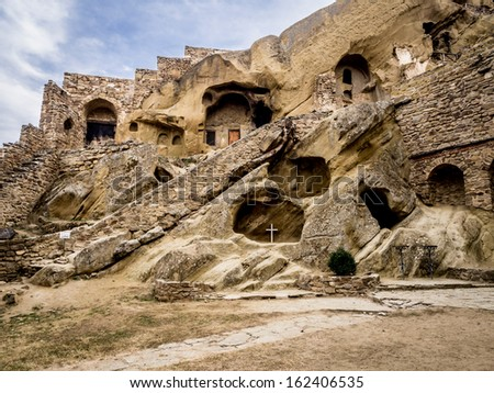 Caves where the monks live seen from the inside in David Gareja, a rock-hewn Georgian Orthodox monastery complex located in the Kakheti region, Republic of Georgia, Caucasus. Landscape orientation. - stock photo
