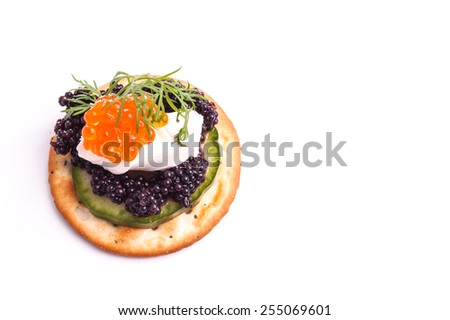 Caviar Appetizer served on crackers isolated on white - stock photo