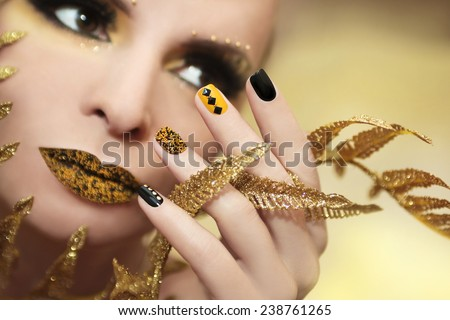 Caviar manicure in yellow black nails with black and gold rhinestones on a brilliant background. - stock photo