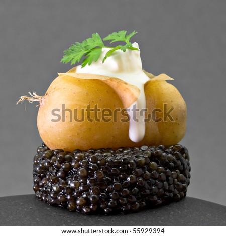 Caviar with potato and fresh cream - stock photo