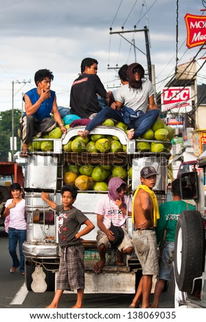 CAVITE, PHILIPPINES - MAY 14: Filipino workers escort a coconut packed Jeepney on May 14, 2009 in Cavite. The Philippines is the world's top producer of coconuts, in 2009 they produced 19,500,000 tons - stock photo
