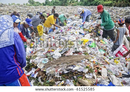 CAVITE, PHILIPPINESS. - FEB 12: Unidentified scavengers rummage for recyclable items on February 12, 2010 in Cavite, Philippines.  Poverty and garbage disposal are major issues in the Philippines.