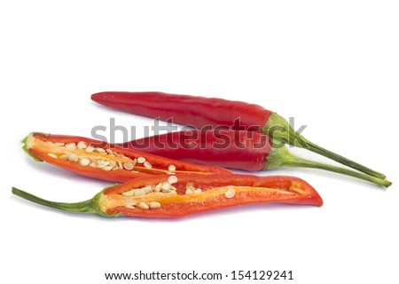 Cayenne pepper, whole and cut in half on a white background - stock photo