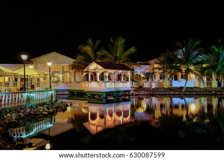 Cayo Coco island, memories Caribe hotel, Cuba, June 26, 2016, gorgeous amazing, inviting view of Memories Caribe hotel grounds lighted with various lights, reflected in water at evening time in garden