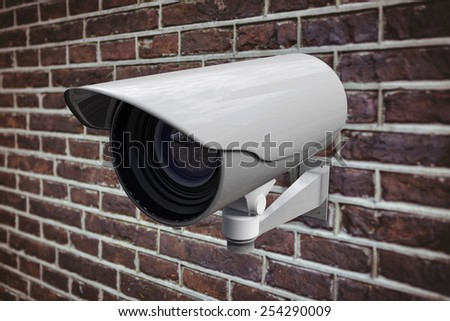 CCTV camera against red brick wall