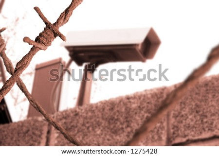 CCTV camera and barbed wire in sepia - stock photo