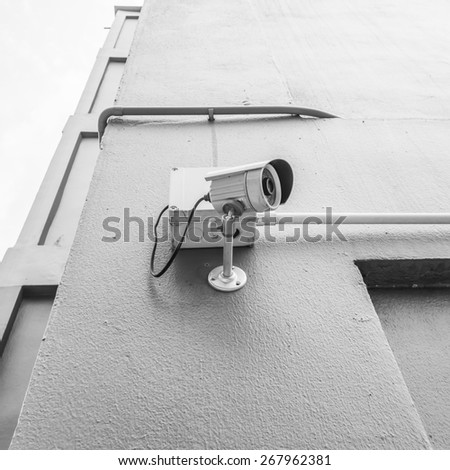 cctv camera install the wall outside building with black and white color tone