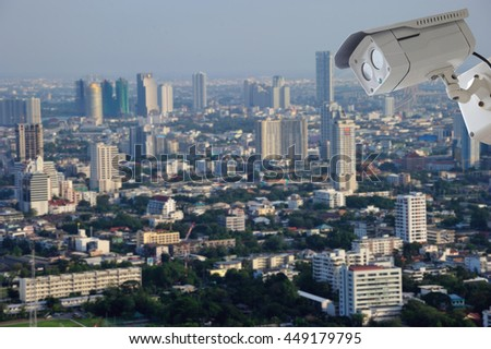 cctv camera isolated on white background with modern building blur background - stock photo